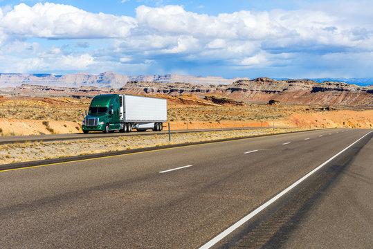 Desert Highway - A semi-trailer truck driving on Interstate Highway I-70 in colorful desert land, Utah, USA.
