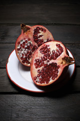 Close-up of sliced pomegranate in plate on wooden table