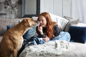 Hübsche rothaarige Frau sitzt auf einem Sofa lacht und wird von einem Hund angestupst