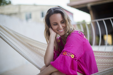 Smiling woman looking away while sitting in hammock at tourist resort