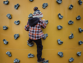 Rear view of boy climbing wall at health club