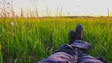 Male feet on green grass at sunset