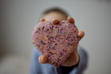 Boy holding heart shape sweet food at home