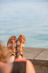 Close up of young woman resting her legs in leather sandals at sea shore, back view with arm and legs of unidentifiable woman