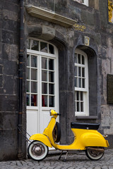 A yellow retro style scooter parked in Essen