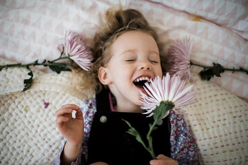 Overhead view of cheerful girl with gerbera lying on bed at home