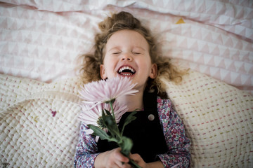 Overhead view of cute cheerful girl with gerbera lying on bed at home