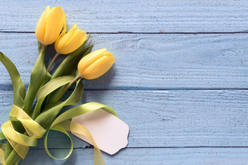 yellow tulip flowers and a blank card on a blue wooden background with copy space, top view from...