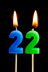 Burning candles in the form of 22 twenty two (numbers, dates) for cake isolated on black background. The concept of celebrating a birthday, anniversary, important date, holiday, table setting