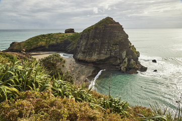 The surfers' paradise and volcanic black sand beach at Piha, showing Lion Rock, a monolith housing many Maori carvings, Auckland area, North Island, New Zealand, Pacific