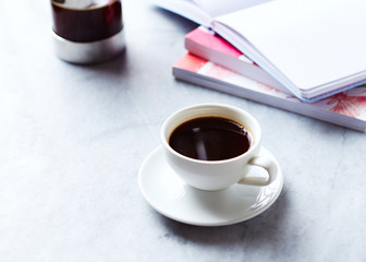 Cup of Black Coffee, books and coffee press on gray marble background