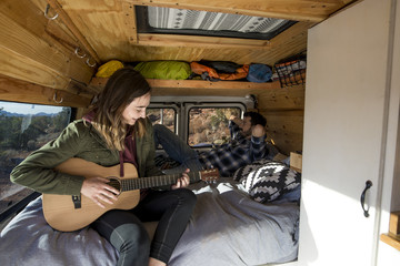 Woman playing guitar while sitting with friend in motor home