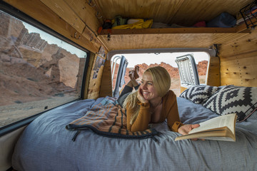 Happy woman holding book while looking through window in motor home