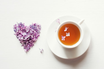 Cup of tea on a saucer and heart from flowers of a lilacin on a white board, top view