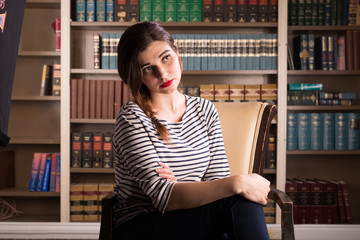 Young caucasian woman dressed in mid century casual fashion poses in a library