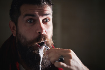 Silly bearded man brushing teeth in bathroom mirror. Young man at home cleaning teeth in the morning. Foam on a beard, emotion, healthcare, good morning, toothpaste, toothbrush.