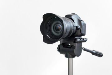 Professional black DSLR mirrorless camera on tripod on white background. Blogging and video recording or photo shooting.