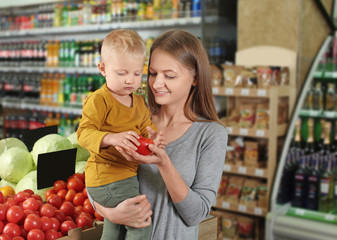 Young mother with little son choosing food in supermarket