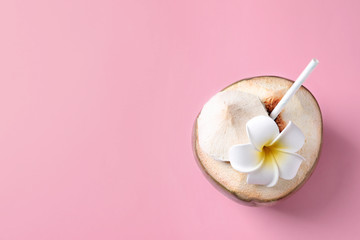 Fresh green coconut with drinking straw and flower on color background, top view