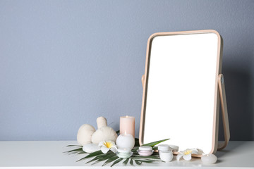 Stylish mirror, cosmetic products and aroma candles on table near light wall