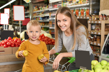 Young mother with little son choosing pears in supermarket