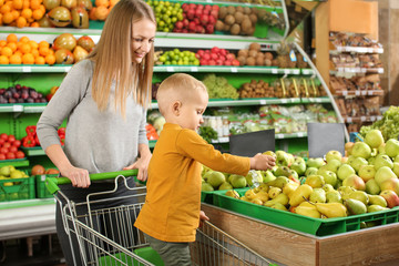 Young mother with little son choosing apples in supermarket
