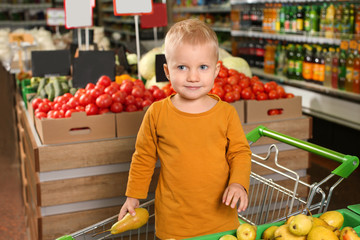 Cute little boy with pear in shopping cart at supermarket