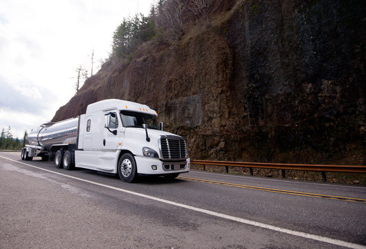 Big rig semi truck tractor transporting tank semi trailer on winding mountain road