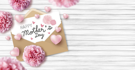 Happy mother's day on white paper in brown envelope and pink heart and carnation flowers on wood texture background with copy space