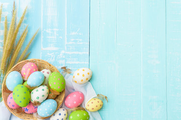 Happy easter! Colorful of Easter eggs in nest with paper star, flower and Feather on pastel color bright blue and white wooden background.