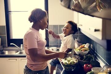 Kid feeding mom in the kitchen