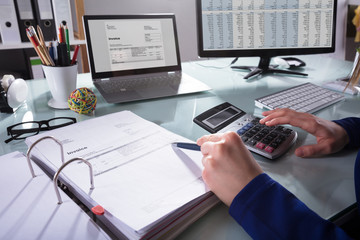 Businessperson Calculating Invoice