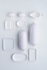 Top view of the composition of white dishes and sausages in a laconic style. Flat lay.