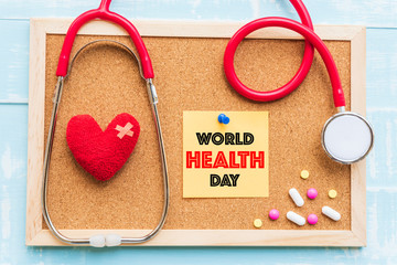 World health day, Healthcare and medical concept. Red heart with Stethoscope, handmade globe, thermometer and yellow Pill on blue Pastel wooden background.