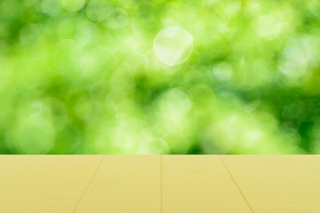 Pastel pink wooden table and blur nature tree green background with spring or summer.