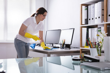 Woman Cleaning Computer In Office