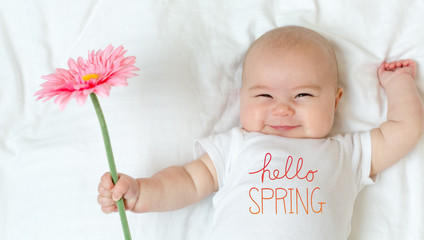 Hello Spring message with baby girl holding a flower