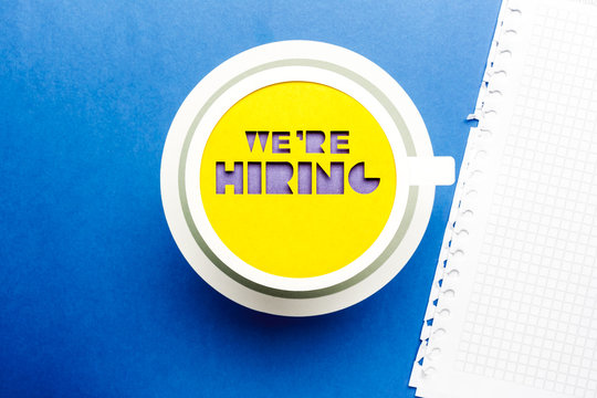 We are hiring concept. Yellow paper cup on blue background.