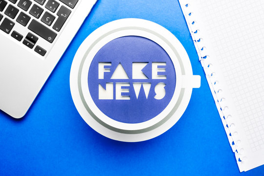 Social media fake news concept. Blue paper cup on blue background