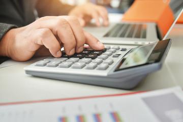 Businessman hand are using a calculator.
