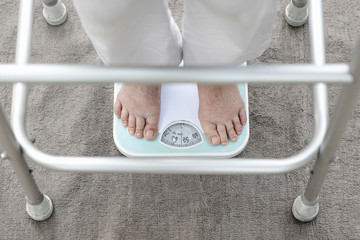 Eldely female standing on weight scale , her weight measure  54 kg.