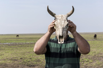 Young man holding a cow skull in front of his head