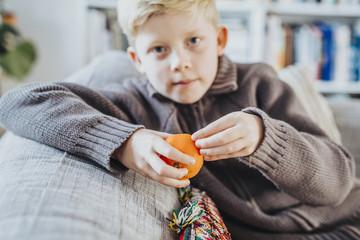 Boy peeling clementine