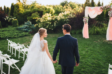 Beautiful newlyweds go hand in hand at the wedding ceremony. The wedding ceremony is green in the garden. Wedding decorations. Solar wedding in the park.
