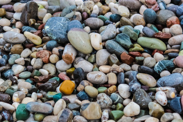 Different colored small sea stones on coast close up horizontal view.