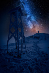 Fototapete - Man looking from mountain to the milky way in winter