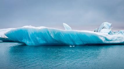 Blue iceberg floating on lake in Iceland