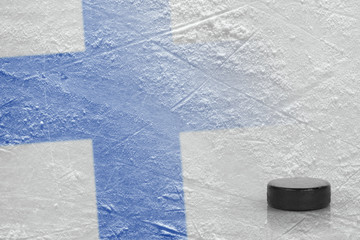 Hockey puck and the image of the Finnish flag on the ice
