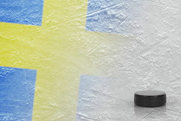 Hockey puck and the image of the Swedish flag on the ice