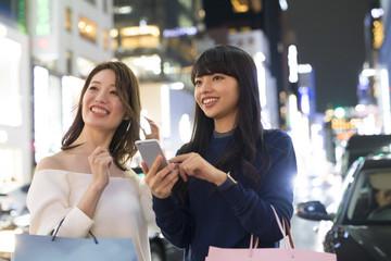 買い物中の女性たちがスマートフォンで場所を探している。